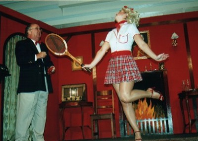 """Tennis Anyone?"" asks Felicity (Lynsey Collis) of Birdboot (Chris Crowley)"