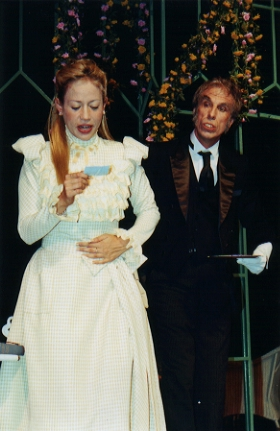 Merriman (Barry Daniel) brings Cecily Cardew  (Elise Meleisea) Algy's card.