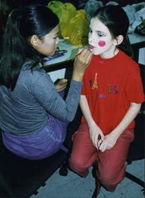Make-up is applied to Sascha Silberstein in the children's munchkin chorus